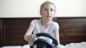 Little girl playing game. Little girl playing game with steering wheel stock video footage