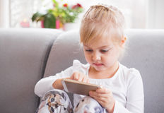 Little girl playing games on smartphone mobile phone outdoor. Technology generation. Stock Image