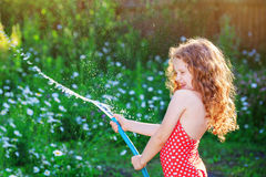 Little girl playing with a garden hose. Curly little girl watering plant in garden at summer day stock images