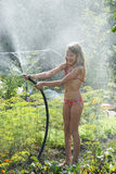 Little girl playing with garden hose Stock Photography