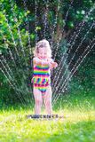 Little girl playing with garden sprinkler. Funny laughing little girl in a colorful swimming suit running though garden sprinkler playing with water splashes royalty free stock photos