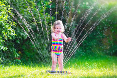 Little girl playing with garden sprinkler Royalty Free Stock Image