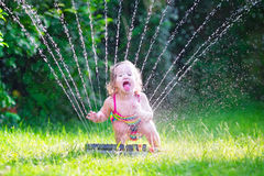 Little girl playing with garden sprinkler. Funny laughing little girl in a colorful swimming suit running though garden sprinkler playing with water splashes stock image