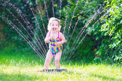 Little girl playing with garden sprinkler. Funny laughing little girl in a colorful swimming suit running though garden sprinkler playing with water splashes stock images