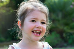 Little girl playing in the garden. Little girl in a vest in the garden in the summer, smiling, close up, selective focus Royalty Free Stock Photos
