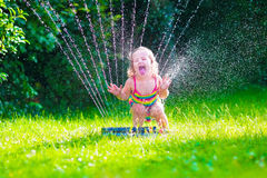 Little girl playing with garden water sprinkler. Child playing with garden sprinkler. Kid in bathing suit running and jumping. Kids gardening. Summer outdoor royalty free stock images