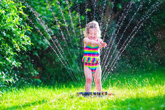 Little girl playing with garden water sprinkler Royalty Free Stock Images