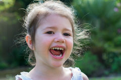 Little girl playing in the garden. Little girl in a white top in the garden in the summer, smiling, selective focus Royalty Free Stock Photos