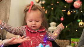Little girl playing with garlands with adults. A little girl holding a garland on the background of a Christmas tree royalty free stock image