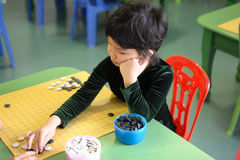Little girl playing go game. A little chinese girl learning to play go(weiqi) game Royalty Free Stock Photos