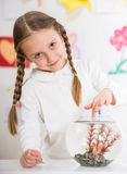 Little girl playing with gold fish Stock Images