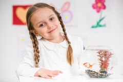 Little girl playing with gold fish Stock Photo