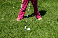 Little girl playing golf. A little girl practicing her golf swing Royalty Free Stock Images