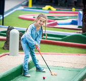 Little girl playing golf Stock Photos