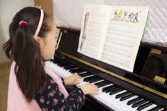 Little girl playing the piano at home. Little girl playing the grand piano at home ,Young girl sitting at a piano keyboard Stock Photography
