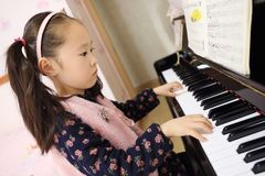 Little girl playing the piano at home. Little girl playing the grand piano at home ,Young girl sitting at a piano keyboard Royalty Free Stock Photos