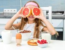 Little girl playing grapefruit Royalty Free Stock Photos