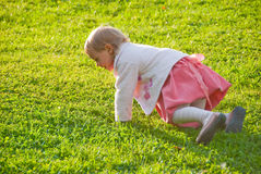 Little girl playing on the grass Stock Photos