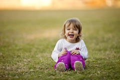 Little girl playing in grass, laughing Royalty Free Stock Image