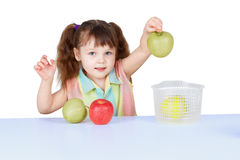 Little girl playing with green apples Royalty Free Stock Photos