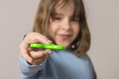 Little girl playing with green fidget spinner toy stock image