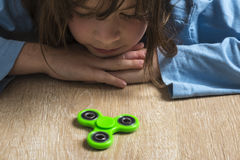 Little girl playing with green fidget spinner toy royalty free stock photos