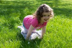 Little girl playing at the green lawn royalty free stock photo