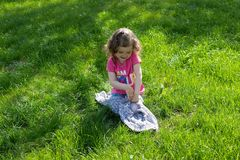 Little girl playing at the green lawn stock photo