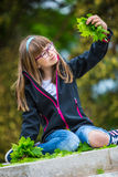 Little girl playing the green maple leaf. In the hands of a bunch of green maple leaf. Stock Image