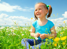 Little girl is playing on green meadow Royalty Free Stock Images