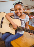 Little girl playing guitar in classroom Royalty Free Stock Photo