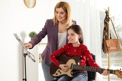 Little girl playing guitar with her teacher. Learning notes stock images