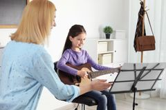 Little girl playing guitar at music lesson. Learning notes royalty free stock photo