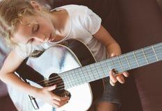 Little girl playing guitar. Stock Image