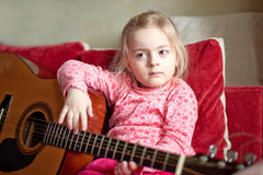 Little girl playing guitar Royalty Free Stock Photos