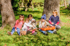 Little girl is playing guitar to a group of friends and a husky Stock Photos