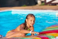 Little girl playing and having fun in swimming pool with air mat Stock Photos