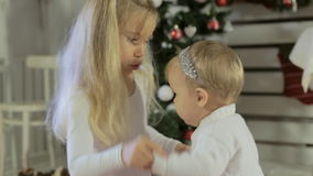 Little girl playing with her baby sister near. Little charming girl playing with her baby sister near decorated with baubles Christmas tree stock footage