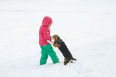 Little girl playing with her dog in a snowy landscape Stock Photos