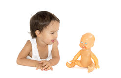 Little girl playing with her doll in studio. isolated Royalty Free Stock Images