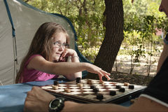 Little girl playing with her father draughts board outdoor camp Stock Image
