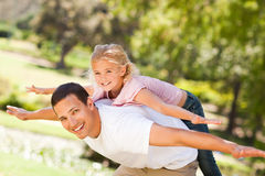 Little girl playing with her father in the park Stock Photos