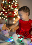 Little girl playing with her first xmas gift. Little girl playing with her first Christmas gift , a baby doll royalty free stock photos