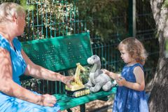Little girl playing with her grandmother at the playground. Royalty Free Stock Image