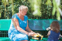 Little girl playing with her grandmother at the playground. Royalty Free Stock Photos