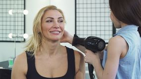 Gorgeous woman smiling while her daughter blow drying her hair royalty free stock photography