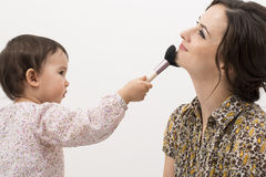 Little girl playing with her mom's makeup isolated Stock Photos
