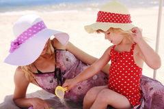 Little girl playing with her mother on the shore of the sea Stock Photography