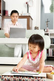 Little girl playing while her mother working royalty free stock photo