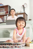 Little girl playing while her mother working stock photos